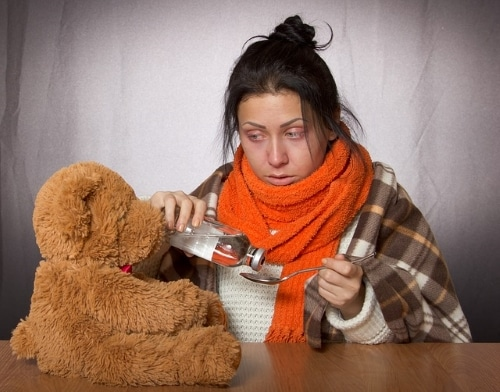 girl with a cold giving medicine to her teddy bear who also has a cold